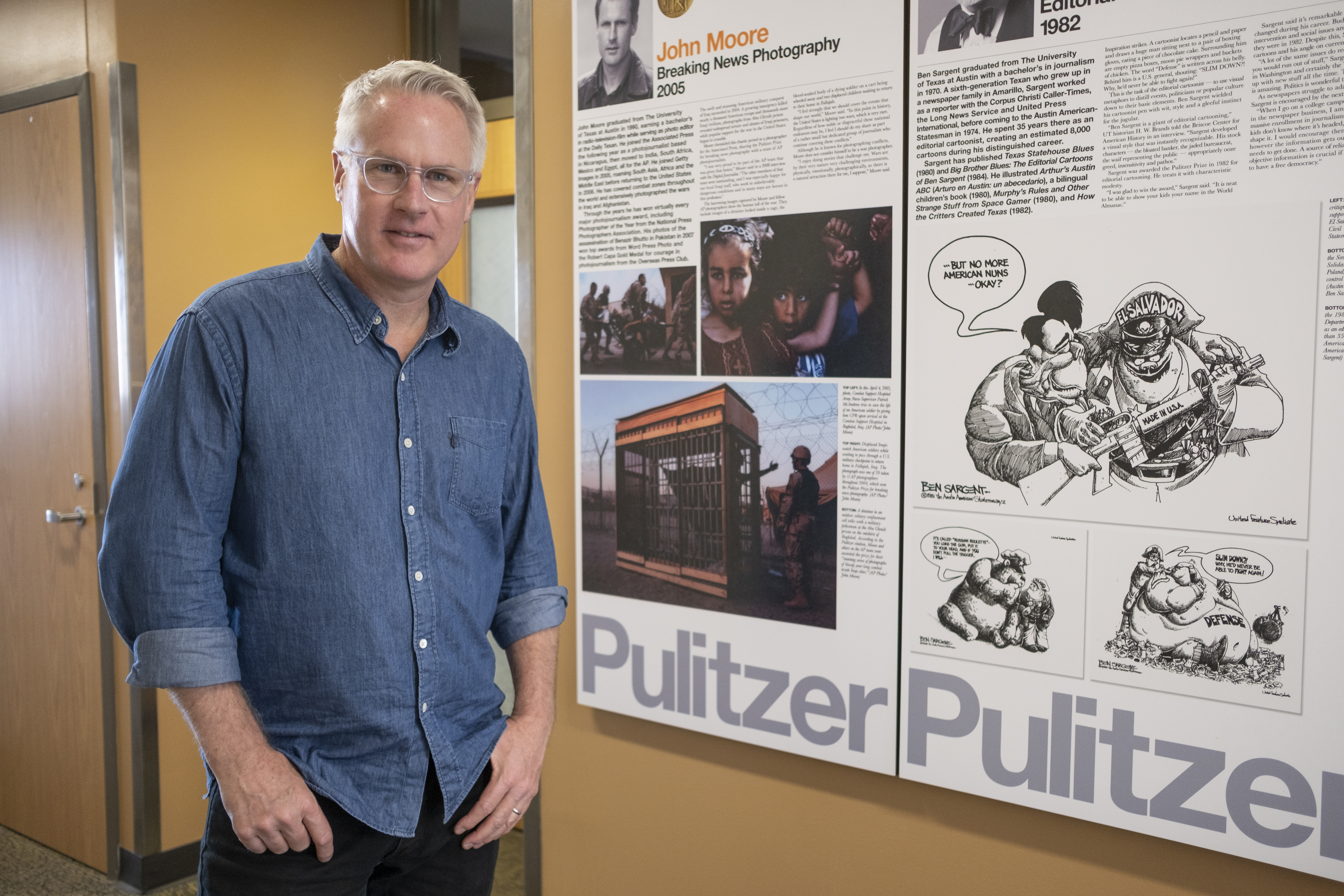 John Moore stands in front of a display of UT Pulitzer winners