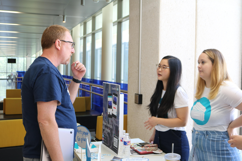 Professor Christian McDonald talks to a student team that built an app called EventPool